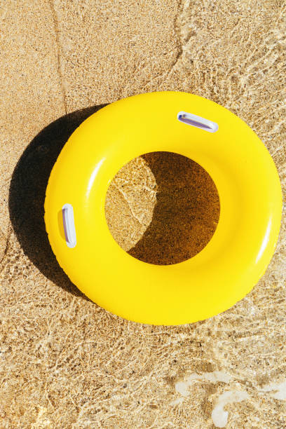 yellow rubber ring floating on the clear shallow sea at pedn vounder beach, cornwall on a bright sunny day. - rubber ring stock pictures, royalty-free photos & images