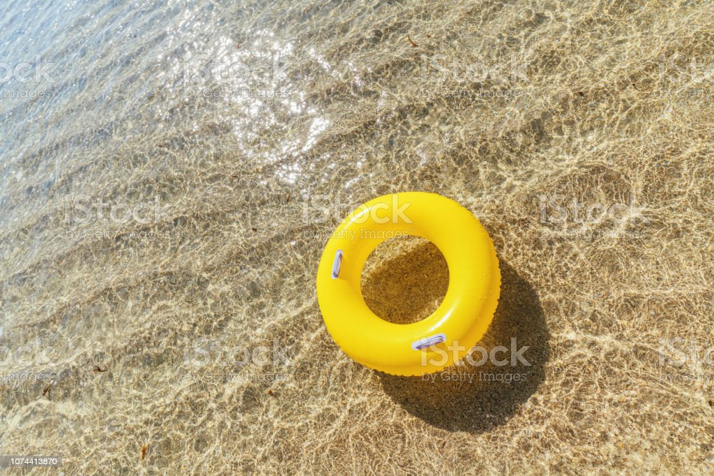 Yellow rubber ring floating on the clear shallow sea at Pedn Vounder Beach, Cornwall on a bright sunny day. stock photo
