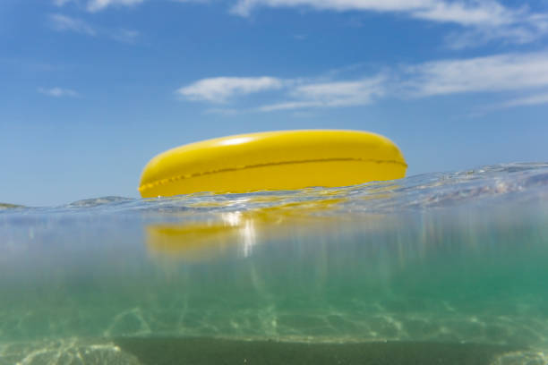 yellow rubber ring floating on the sea, pedn vounder beach - rubber ring stock photos and pictures