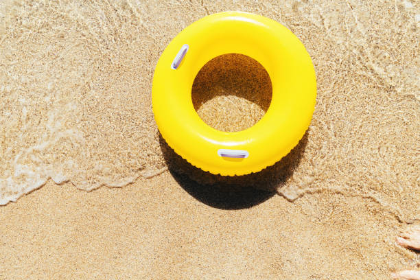 yellow rubber ring on a breaking wave at the waters edge, pedn vounder beach, cornwall on a bright sunny day. - rubber ring stock photos and pictures
