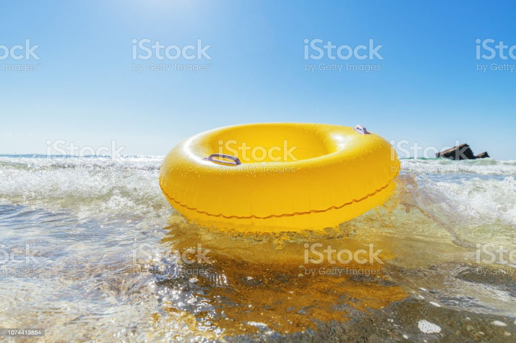 Yellow rubber ring on a breaking wave at the waters edge, Pedn Vounder Beach, Cornwall on a bright sunny day. stock photo