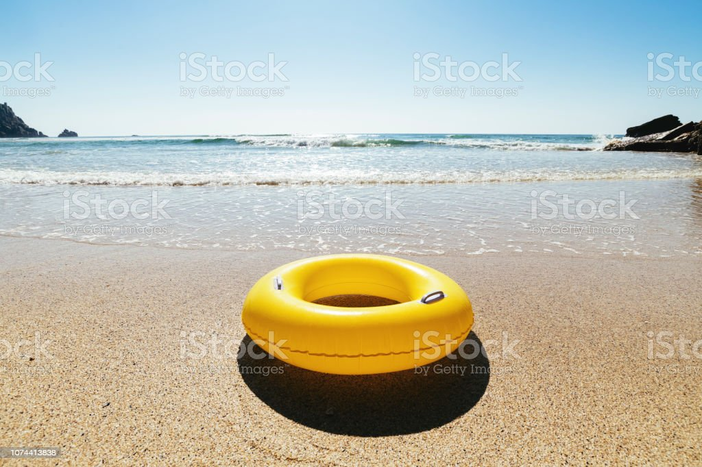 Yellow Rubber ring on the sand at Pedn Vounder Beach, Cornwall on a bright sunny day. stock photo