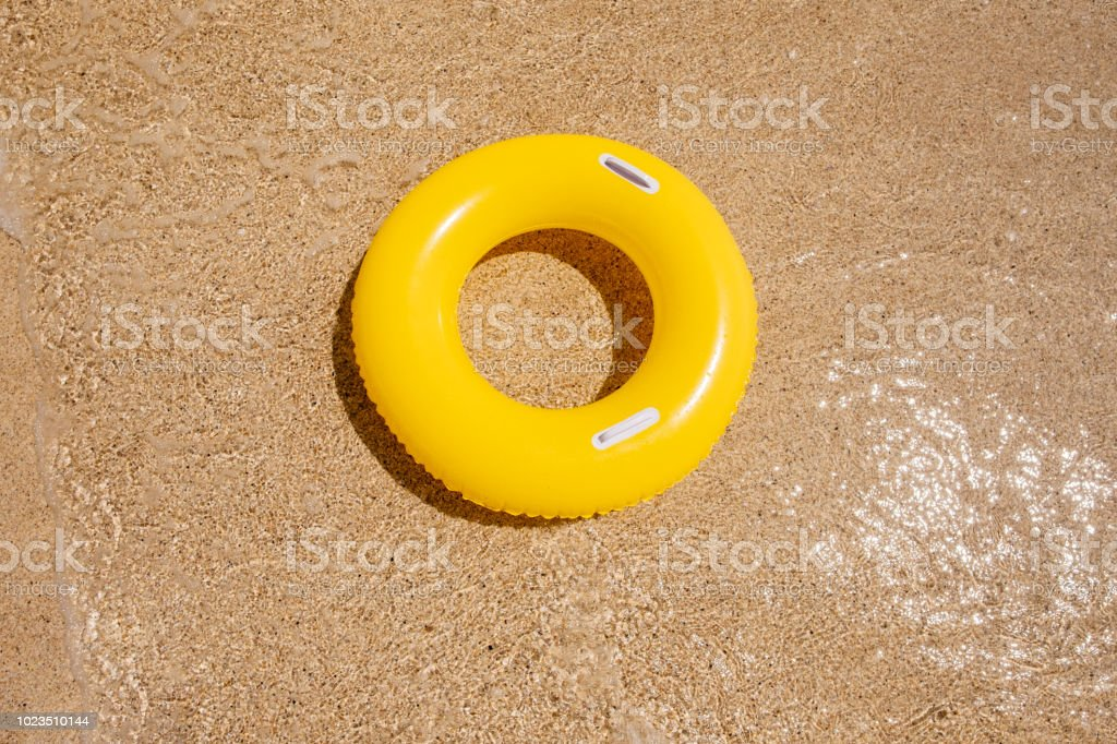 Yellow Rubber ring on the sand at Pedn Vounder Beach, Porthcurno, Cornwall stock photo