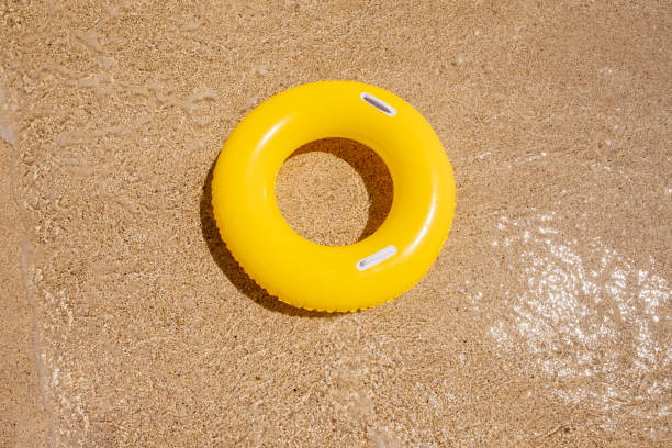 yellow rubber ring on the sand at pedn vounder beach, porthcurno, cornwall - rubber ring stock pictures, royalty-free photos & images