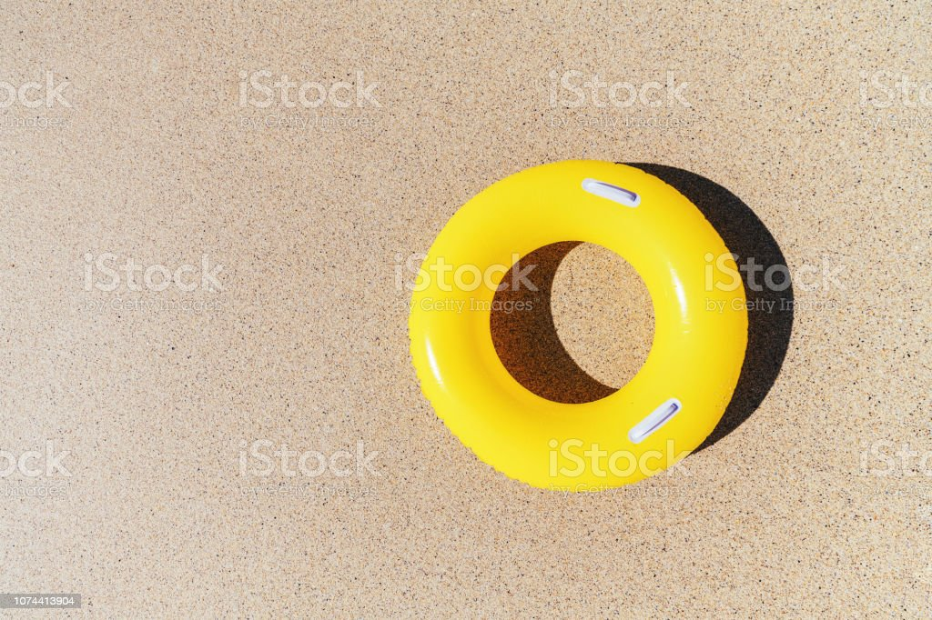 Yellow rubber ring on the sand from above. stock photo