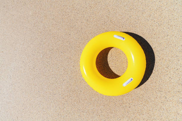 yellow rubber ring on the sand from above. - rubber ring stock photos and pictures
