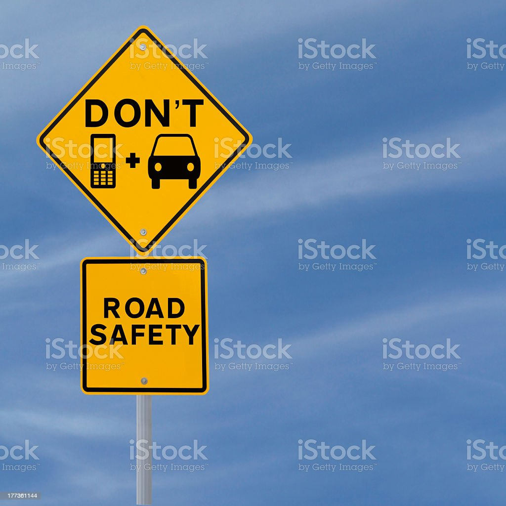 A yellow safety don't text and drive sign stock photo