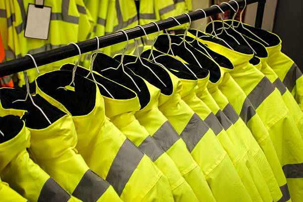 Yellow safety fluorescent jackets Hanged up Yellow safety fluorescent jackets hanged up. Multiple jackets. reflective clothing stock pictures, royalty-free photos & images