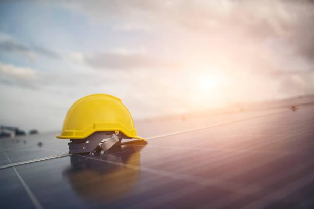 Yellow safety helmet on solar cell panel stock photo