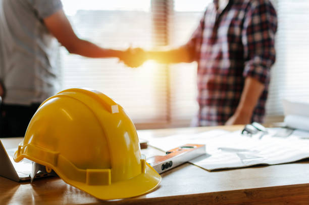 yellow safety helmet on workplace desk with construction worker team hands shaking greeting start up plan new project contract in office center at construction site, partnership and contractor concept yellow safety helmet on workplace desk with construction worker team hands shaking greeting start up plan new project contract in office center at construction site, partnership and contractor concept construction industry stock pictures, royalty-free photos & images