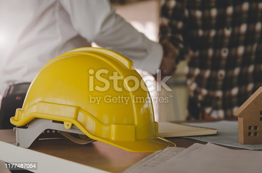 1055059750 istock photo yellow safety helmet on workplace desk with construction worker team hands shaking greeting start up plan new project contract in office center at construction site, partnership and contractor concept 1177487054