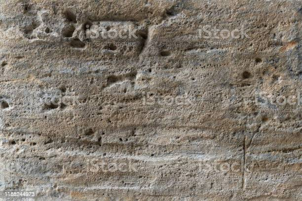 Photo of Yellow sandstone stone, scratched old. Weathered natural stone building retro style. Porous texture background.