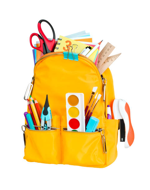 Yellow school backpack with school supplies isolated on white background stock photo