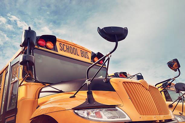yellow school bus against autumn sky - bus scolaires photos et images de collection