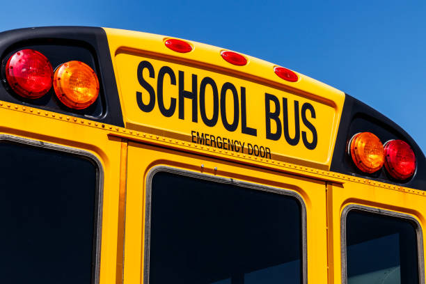 yellow school bus in a district lot waiting to depart for students vi - school buses stock pictures, royalty-free photos & images