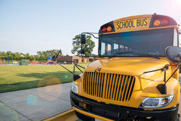 yellow school bus parked next to playground - school bus stock photos and pictures