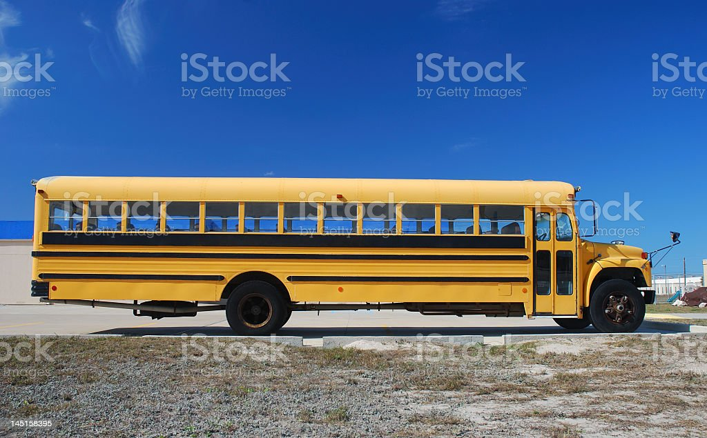 Yellow school bus parked on a beach with blue sky stock photo