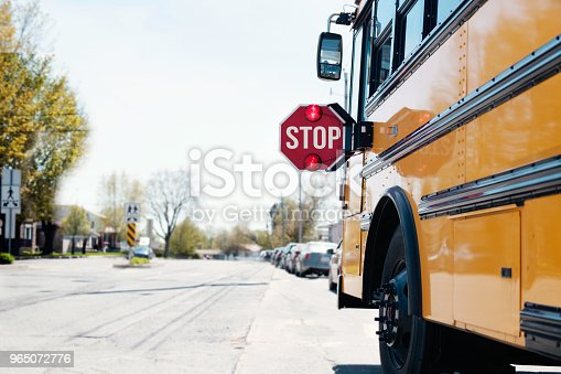 Yellow School bus with stop sigh in the street with red light open. Photo was taken in Canada.