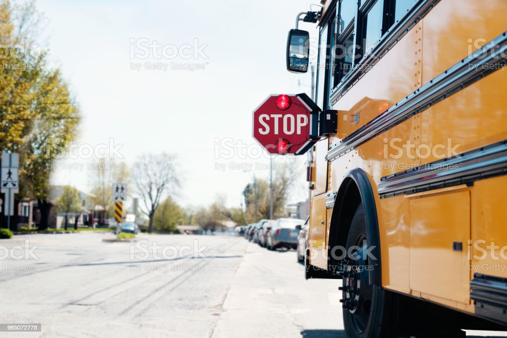 Yellow School bus with stop sign stock photo
