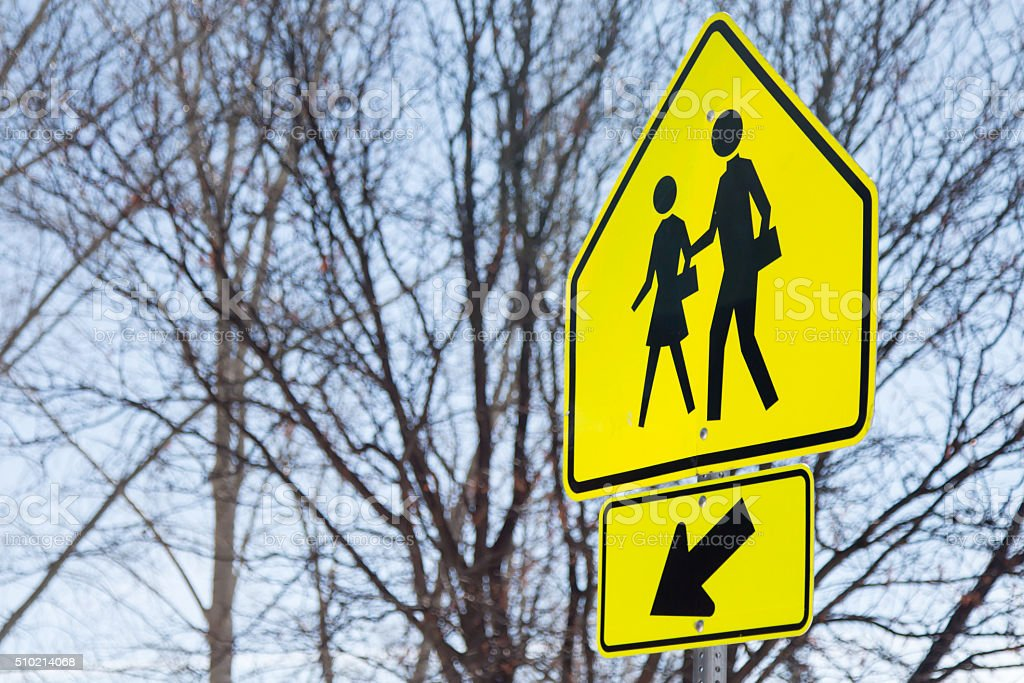 Yellow school crossing sign with arrow stock photo