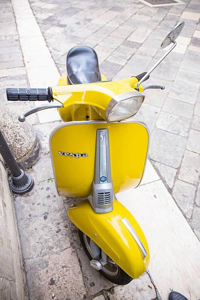 amarillo scooter en la calle. vista frontal - vintage vespa fotografías e imágenes de stock