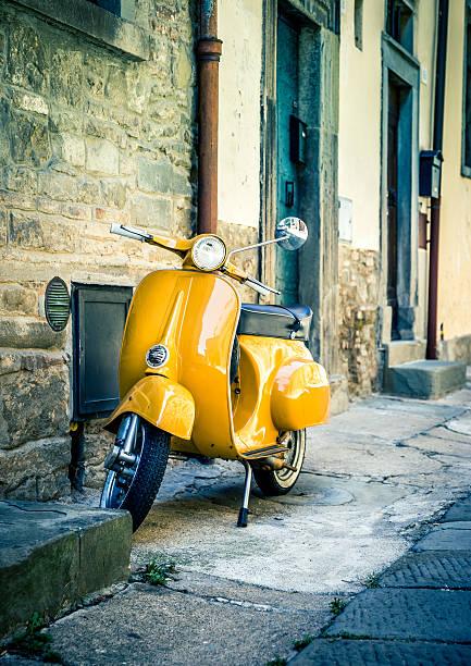 Yellow scooter in tuscan Cortona town stock photo