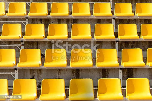 Yellow seats on stands of stadium in open. Rows are horizontal. On seats shade from sun. Front view.