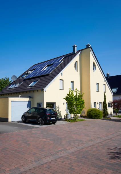 Gelbe Doppelhaushälfte mit Sonnenkollektoren auf dem Dach – Foto