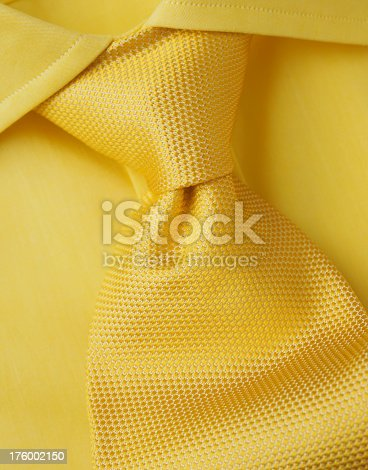 A yellow shirt with a yellow tie in close-up.