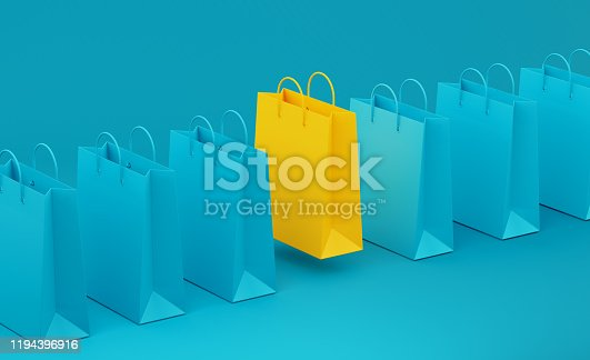 Yellow shopping bag standing out from teal shopping bags over teal background. Horizontal composition with copy space. Standing out from the crowd concept.