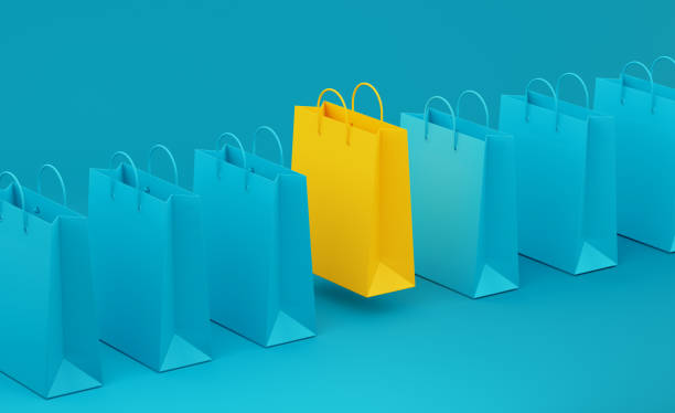 Yellow Shopping Bag Standing Out From Teal Shopping Bags over Teal Background stock photo