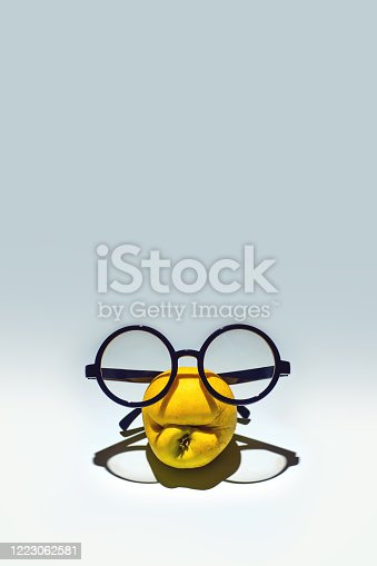 Yellow shrivelled apple with a grimace in glasses. On a light blue background.