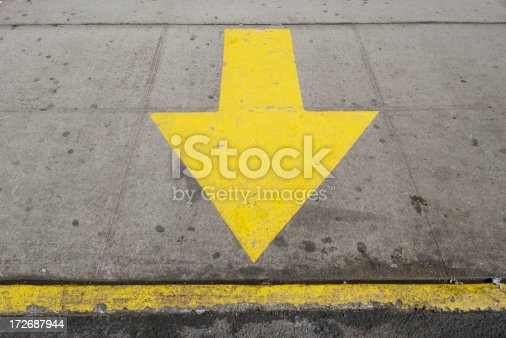 istock Yellow Sidewalk Arrow Points to the Curb 172687944
