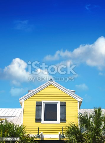 istock yellow siding home over blue sky 183858308