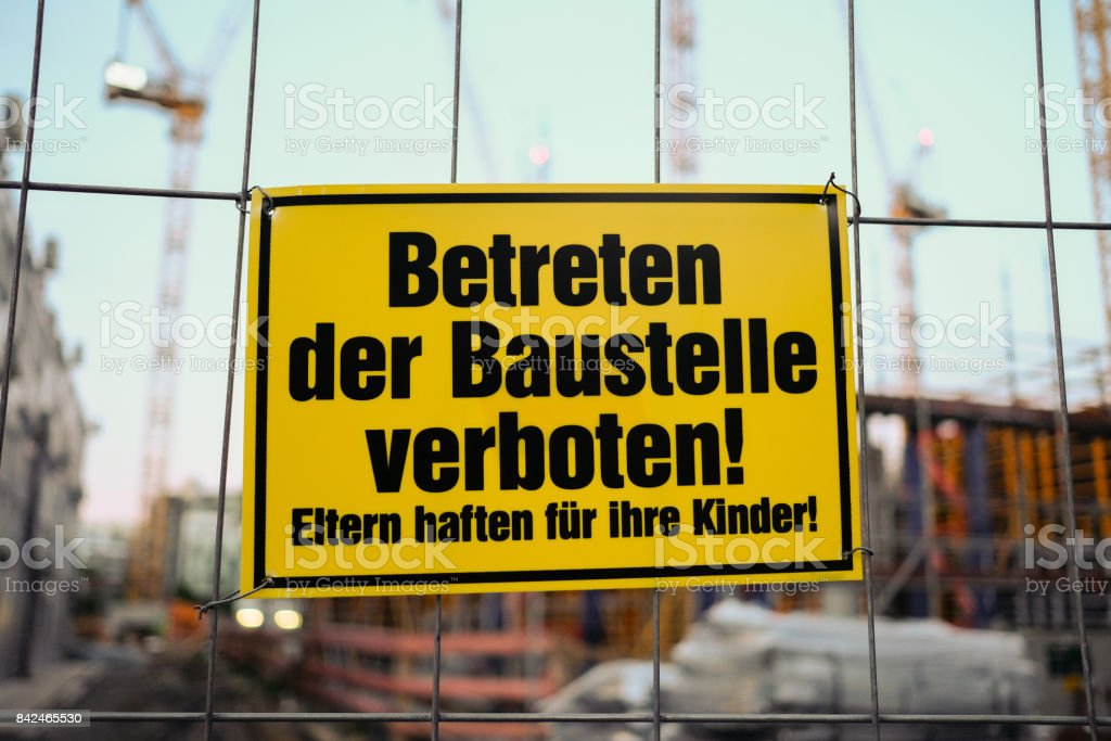 Yellow sign in german: Betreten der Baustelle verboten! Eltern haften fuer ihre Kinder! translation: entering the building site prohibited. Parents are responsible for their children stock photo