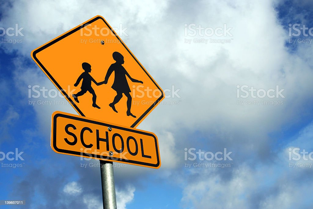 A yellow sign warning of a school zone stock photo