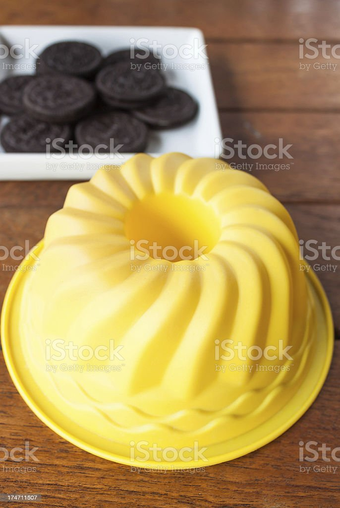 Yellow silicone cake form on wood table royalty-free stock photo