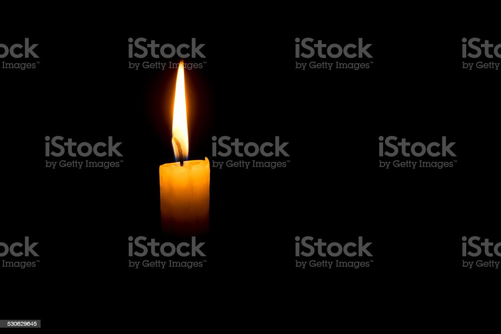Yellow single candle on a dark black background stock photo