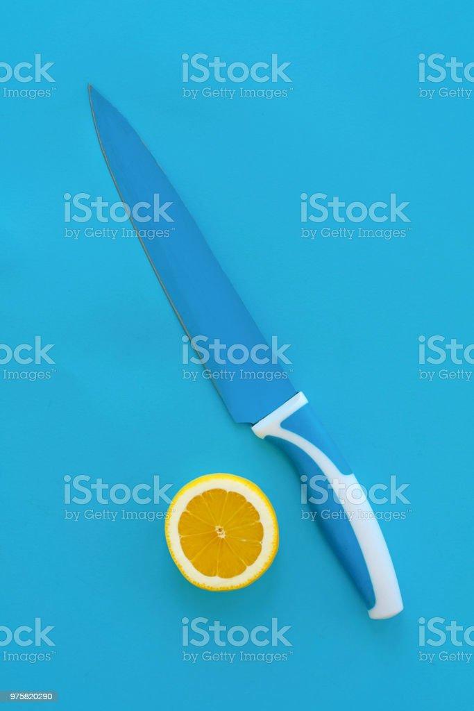 gelbe Scheibe Zitrone und Messer auf leuchtend blauem Papier, legen Sie trendige flach. Früchte modernes Image, Ansicht von oben. saftige Sommer Vitamin Essen und Diät-Konzept. Pop Art-Stil. kreativen Minimalismus - Lizenzfrei Abstrakt Stock-Foto