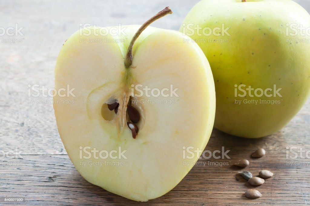 Yellow sliced apple on wooden table stock photo