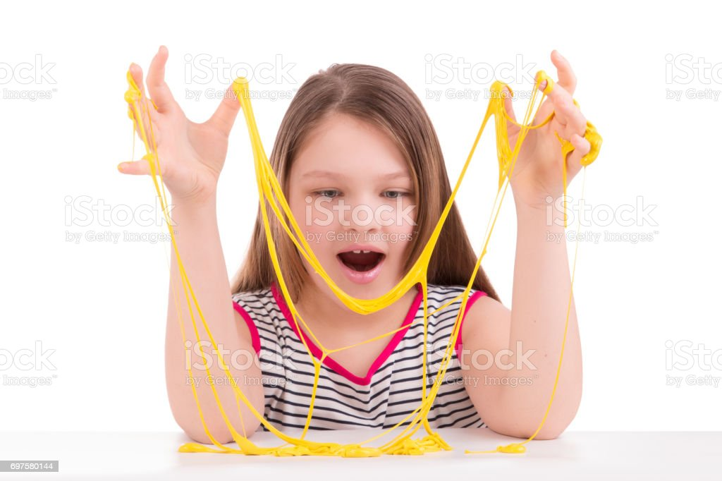 Yellow slime in the hands of a girl stock photo