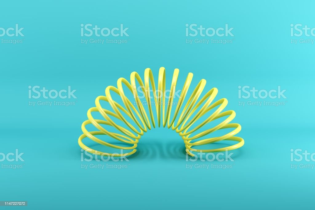 Yellow slinky isolated on blue background. Minimal conceptual idea...