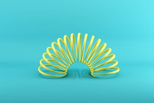 Gelber Slinky isoliert auf blauem Hintergrund. Minimales Ideenkonzept. – Foto