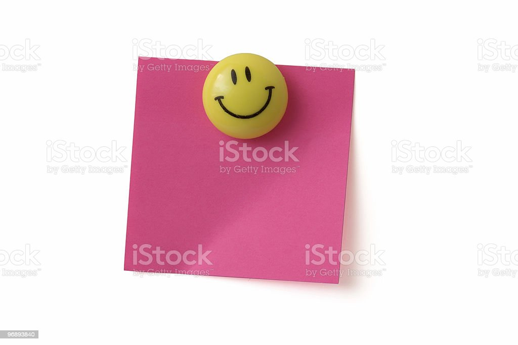 A yellow smiley face magnet holding a pink sticky paper  royalty-free stock photo