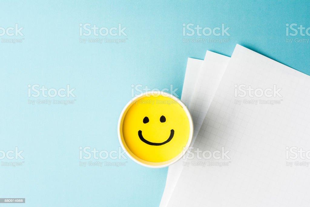 Cara sonriente amarilla, feliz humor, taza de papel y papeles sobre fondo azul. - foto de stock