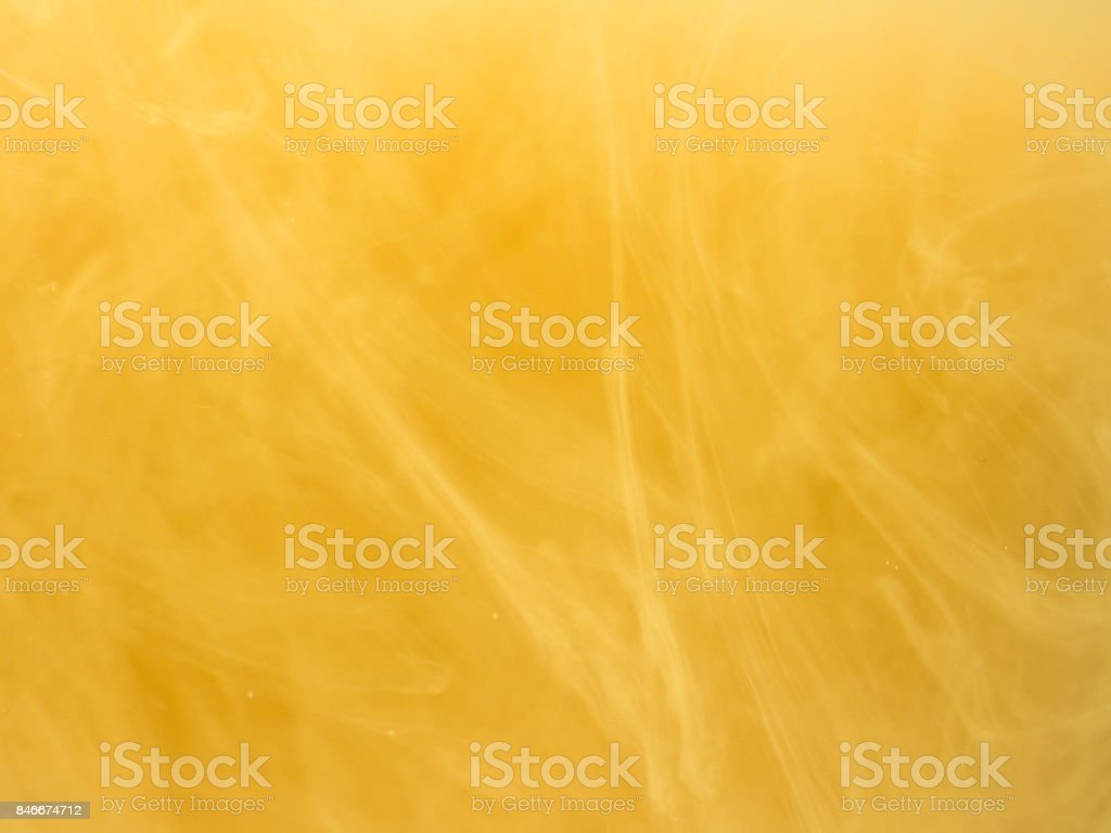 Yellow smoke, ink in water. Abstract colored background. Frozen movement color flow of paint. Horizontal photo with soft focus, blurred backdrop stock photo