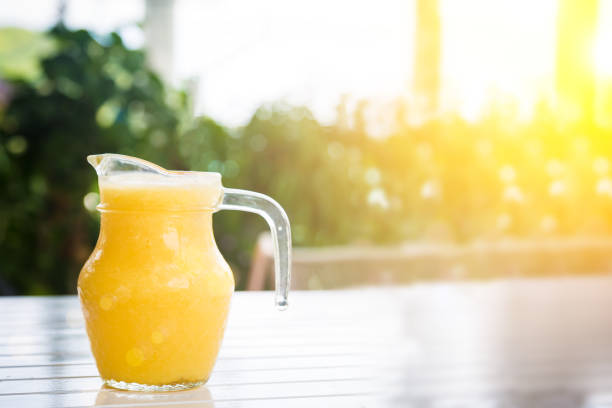 Yellow smoothie from tropical fruits on the white wooden table in jug at sunny day. stock photo