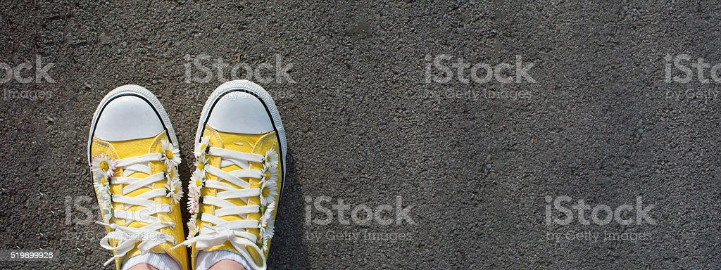 Yellow sneakers decorated with daisies stock photo