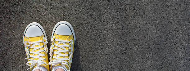 gelbe sneaker mit gänseblümchen - jagd kranz stock-fotos und bilder