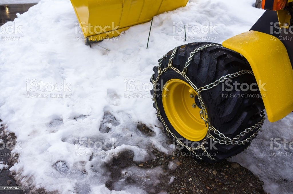 Yellow snowplow truck cleared the snow-covered road in winter day. stock photo